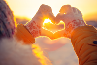Gloved hands in a heart shape against a backdrop of a sunrise