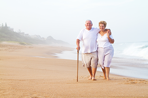 Old man and woman taking a stroll on the beach